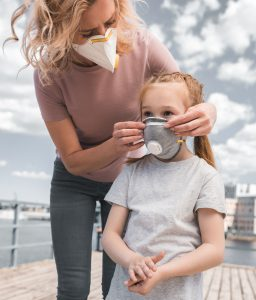 אמא וילדה עם מסכות נגד וירוס הקורונה